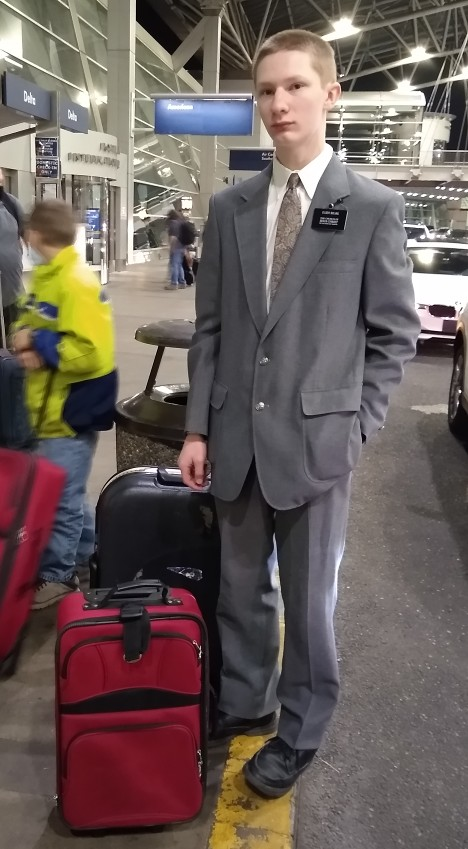 Matthew standing with his luggage